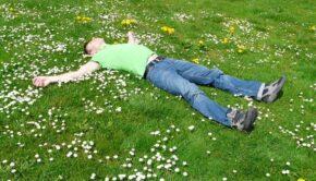 Mand der ligger på græs i haven